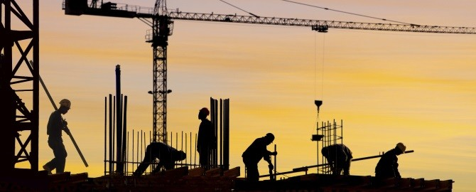 Men working on building site at sunset 670x270